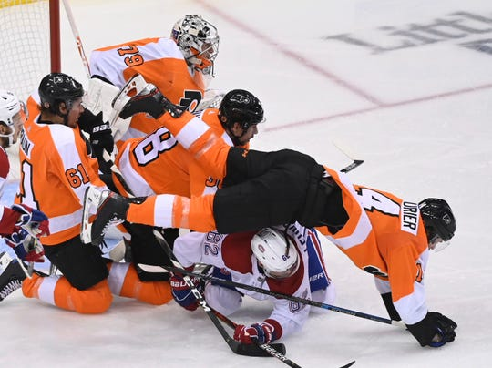 Philadelphia Flyers center Sean Couturier (14) falls over Montreal Canadiens left wing Artturi Lehkonen (62) in front of the net during the second period in Game 5 of an NHL hockey first-round playoff series, in Toronto on Wednesday, Aug. 19, 2020.