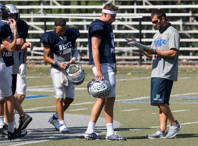 Reitz Panthers head coach Cory Brunson, right, goes over plays with quarterback Reid Brickey, center, during a practice Wednesday afternoon, Aug. 19, 2020. The Panthers face the Harrison Warriors in the season opener Friday evening.