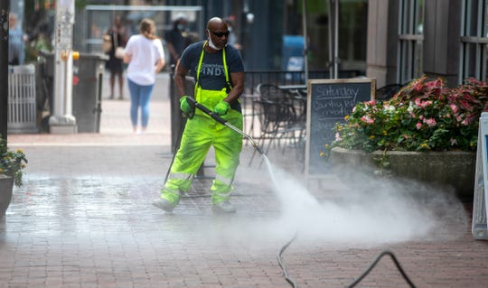 Scott Persons of Downtown Indy cleans sidewalks on Market Street in downtown Indianapolis on Aug. 17, 2020.