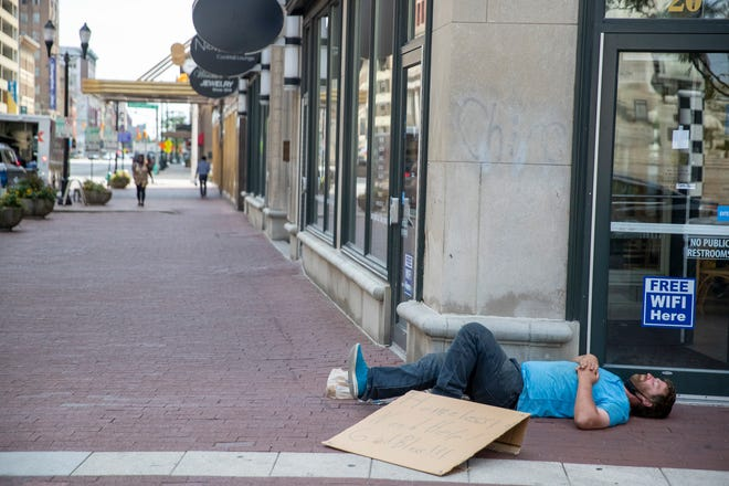 A man with a sign describing himself as homeless naps near the Au Bon Pain on the south side of Monument Circle, Monday, Aug. 17, 2020. Indianapolis has recently installed seven portable toilets to augment the nine already placed throughout Downtown.