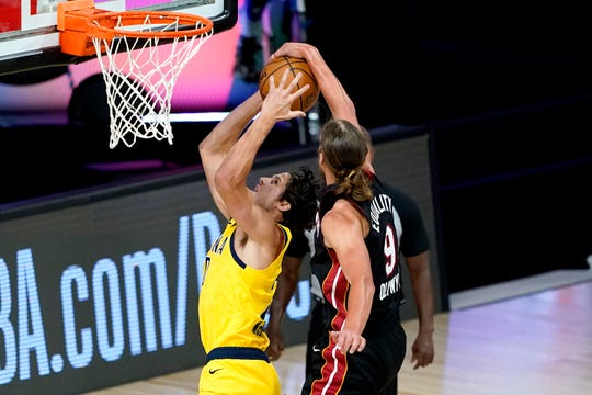 Miami's Kelly Olynyk blocks Indiana's T.J. McConnell in the first half.
