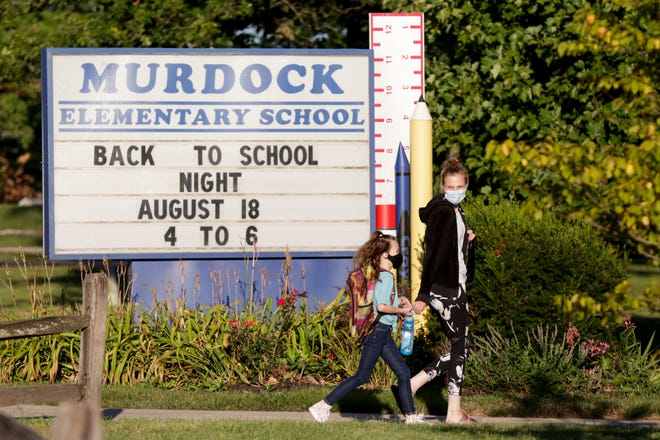 Kelsa Manion walks her daughter Emma Reel towards the front doors of Murdock Elementary school as Emma starts her first day of second grade, Thursday, Aug. 20, 2020 in Lafayette.
