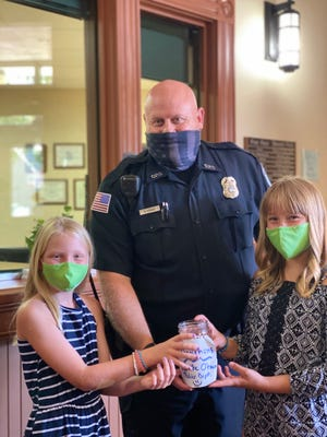 Nola Sprester (left) and Kendra Lauersdorf present a donation collected fro a book drive to Oconomowoc Police Department Officer Pat Hogan. The book drive collected $170 for the department.