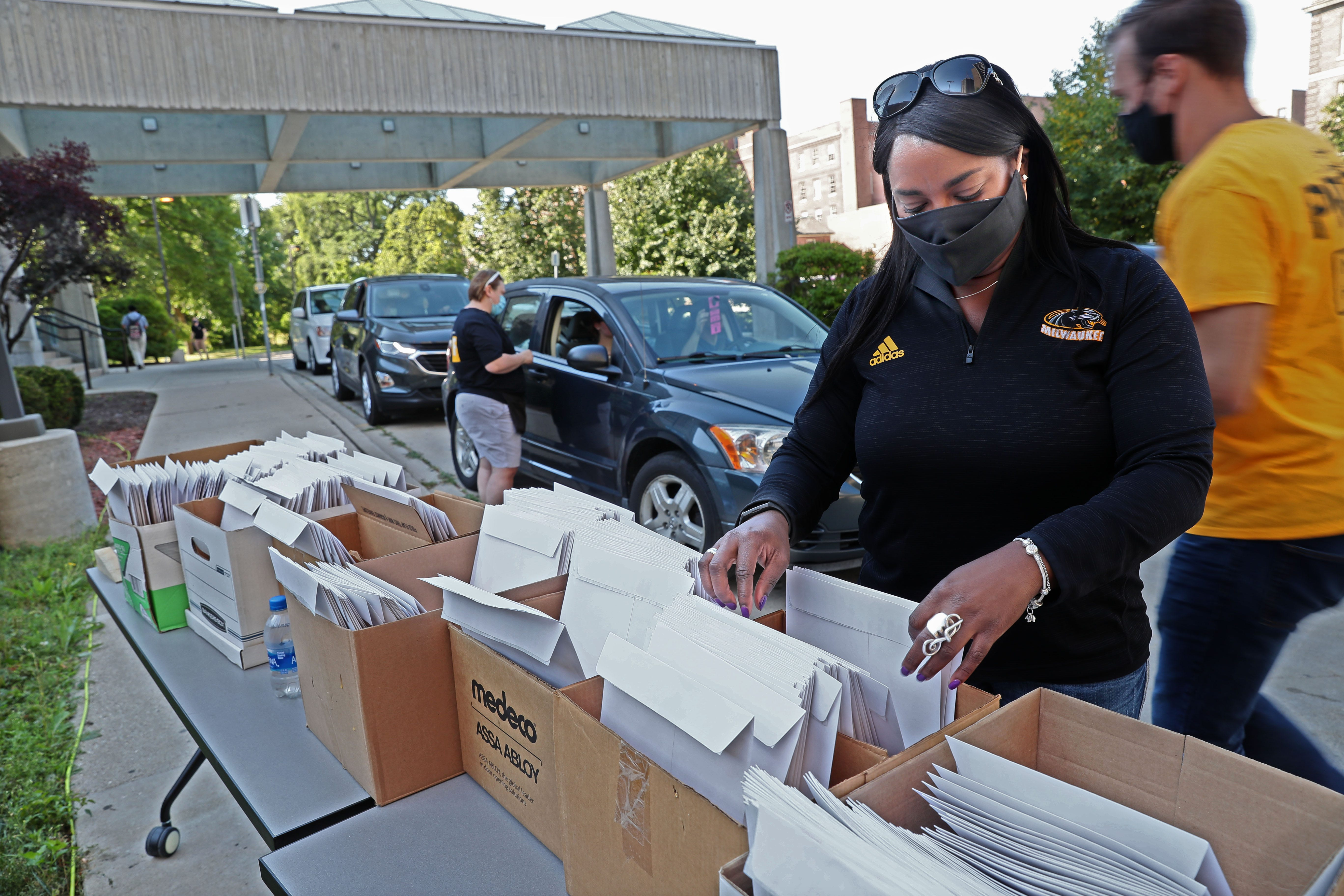 """Arcetta Knautz, director of university housing, helps as students move in at the University of Wisconsin-Milwaukee's Sandburg Residence Hall under COVID-19 restrictions. """"It's sort of like a puzzle,"""" Knautz said. """"We can only have so many people moving in on the hour, on the half hour."""""""
