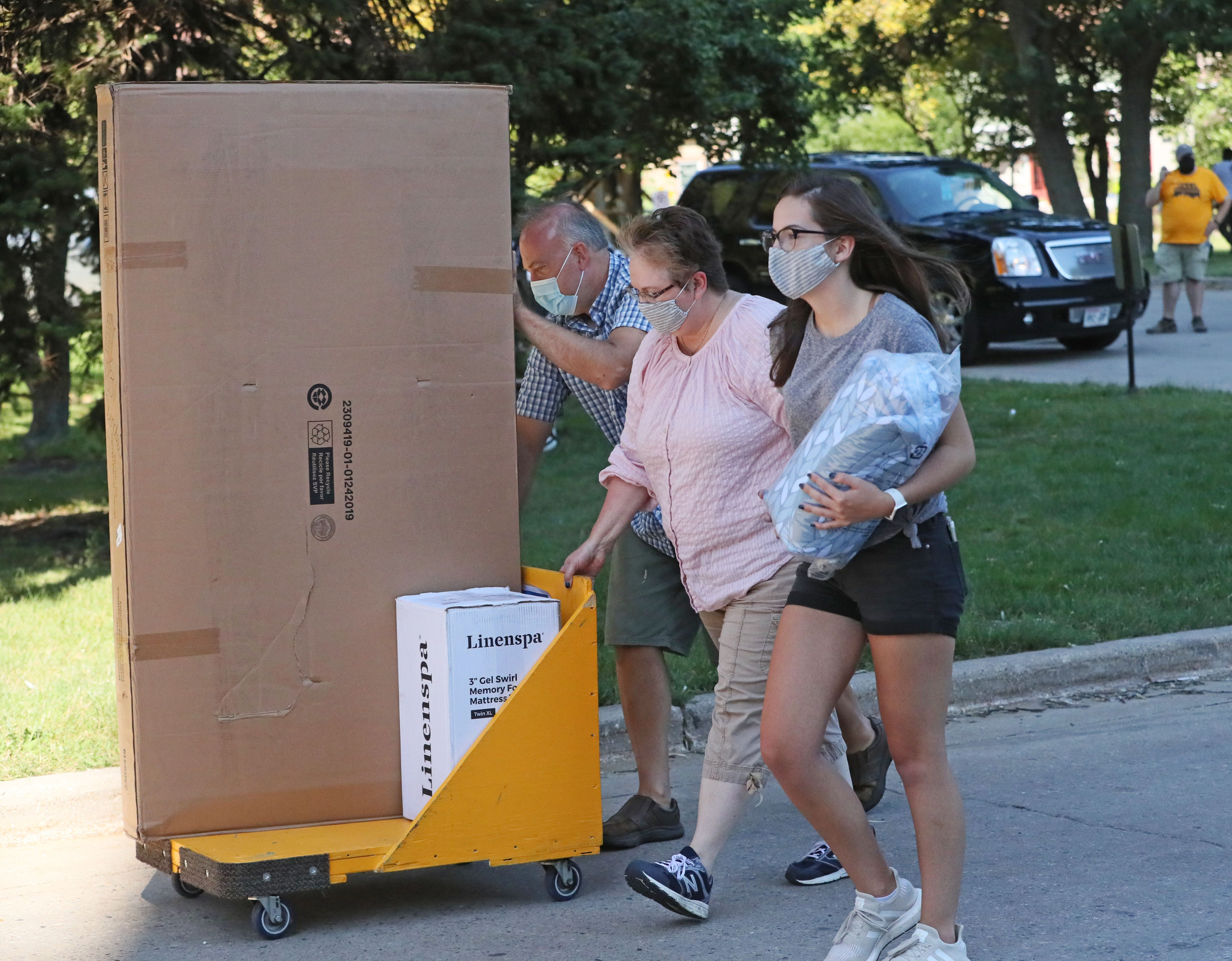 Freshman Makenna Mohr, right, of Green Bay and her parents, Dale Mohr, left, and Donica Mohr, help her move her belongings into the UW-Milwaukee's Sandburg Residence Hall.