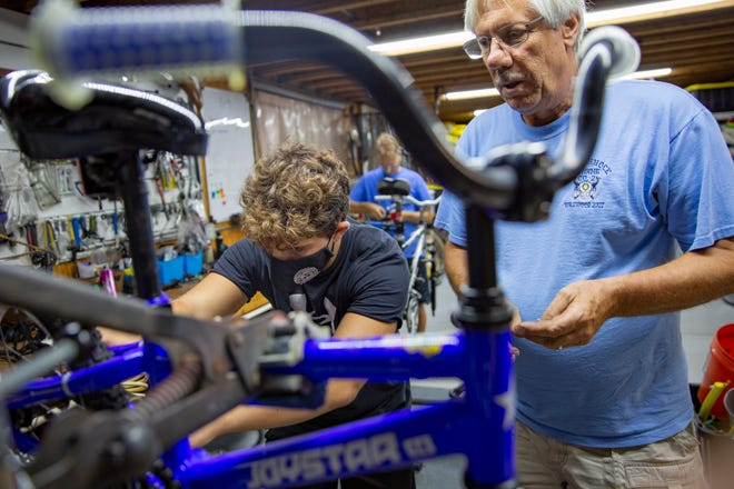 Volunteer Marco Delgrosso, left, and Bikes For Tykes director Bob Kurtz work on a bike, Wednesday, Aug. 19, 2020, at the Bikes For Tykes workshop in North Naples.