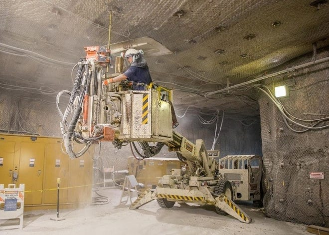Mine operations technician Ben Medina installs a rock bolt in the Waste Isolation Pilot Plant underground. Rock bolts assure ground stability and worker safety in the underground transuranic waste repository.