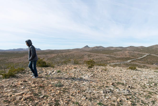 Lordsburg native and art teacher Jessica Mesa walks on a rocky hill overlooking the desert surrounding Lordsburg, in 2019.