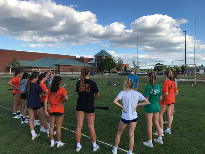 Northville head coach Rick VanDeerVeer addresses his team before an outdoor tryout session.
