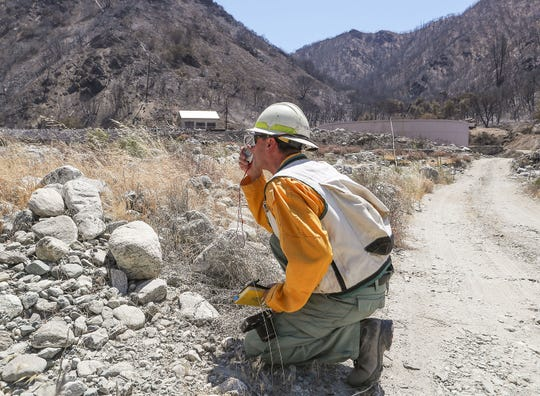 Yanni a with the Burned Area Emergency Response (BAER) team, checks the grade of an area that was burned by the Apple Fire in Banning Canyon, August 14, 2020.
