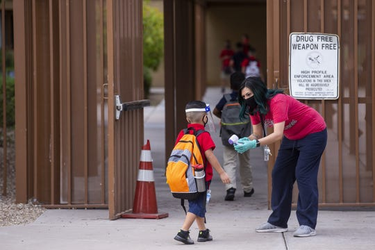 Rubi Gomez, a health aide at Griffith Elementary School, takes students' temperature in Phoenix on August 20, 2020.