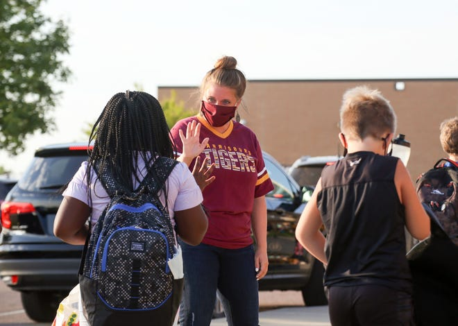 A teacher waves to incoming students on the first day of school on Thursday, August 20, at Freedom Elementary School in Harrisburg.