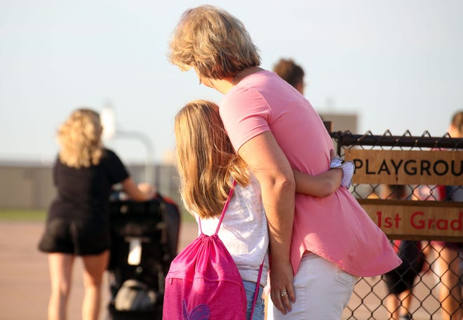 A girl hugs her mother before parting for the first day of school on Thursday, August 20, at Freedom Elementary School in Harrisburg.
