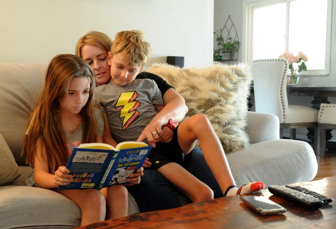 "Camryn Sheehan, 10, her mother Jamie Sheehan, and her brother Todd Sheehan, 7, read ""Diary of a Wimpy Kid: The Getaway."" Jaime took a leave of absence from her job at a local bank to take care for her children while they're home from school. Her husband is a plumber and makes more so it made more sense financially for her to stay home."