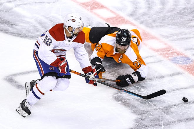 The Canadiens' Tomas Tatar and the Flyers' Claude Giroux battle for the puck during Game 5 on Wednesday night in Toronto.