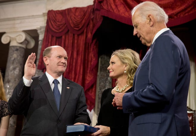 FILE - In this Jan. 6, 2015, file photo, Vice President Joe Biden administers the Senate oath to Sen. Chris Coons, D-Del., as Coons' wife, Annie Coons, watches during a ceremonial re-enactment swearing-in, in the Old Senate Chamber on Capitol Hill in Washington. When Coons speaks to the Democratic National Convention on Thursday, Aug. 20, before Biden's speech accepting the party's presidential nomination, his remarks will focus on faith - attesting in highly personal fashion to his longtime friend's belief in God. (AP Photo/Jacquelyn Martin, File)