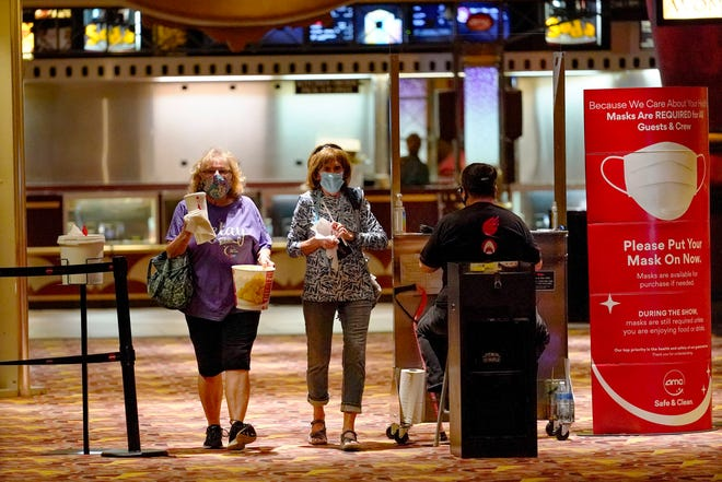 """Betty Gallagher, left, carries popcorn and drinks beside Mary MacBeth as they head in to see, """"I Still Believe"""" at the AMC theatre in West Homestead, Pa., which reopened Thursday for the first time since the start of the COVID-19 pandemic."""
