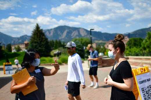 An incoming freshman queries a university employee upon arriving on campus at University of Colorado Boulder on August 18, 2020 in Boulder, Colorado. Due to the coronavirus pandemic, many colleges and universities are instituting different strategies this fall semester, with most students living on campus attending all classes with remote instruction.
