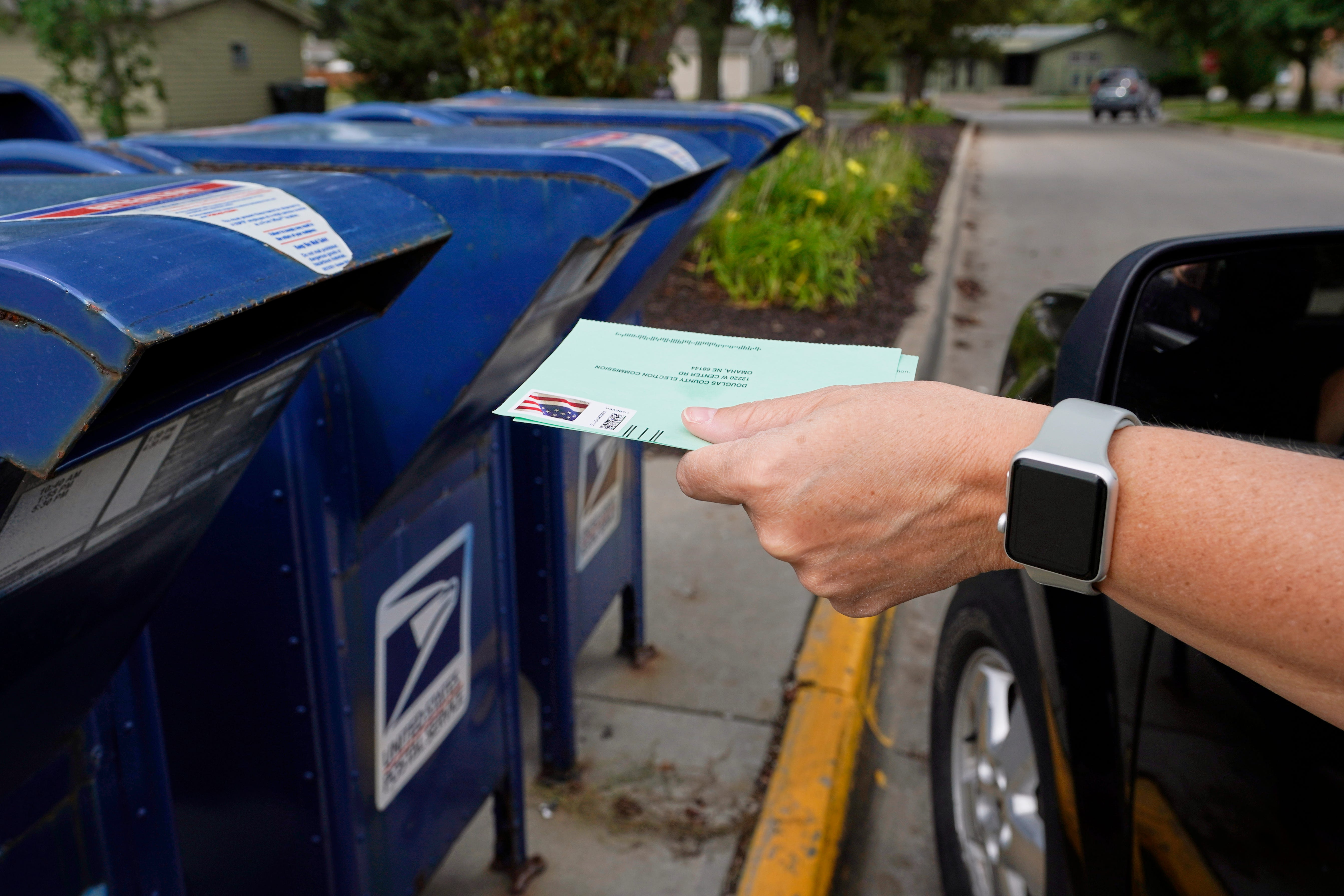 A person drops applications for mail-in-ballots into a mail box in Omaha, Neb. U.S. Postal Service warnings that it can't guarantee ballots sent by mail will arrive on time have put a spotlight on the narrow timeframes most states allow to request and return those ballots.