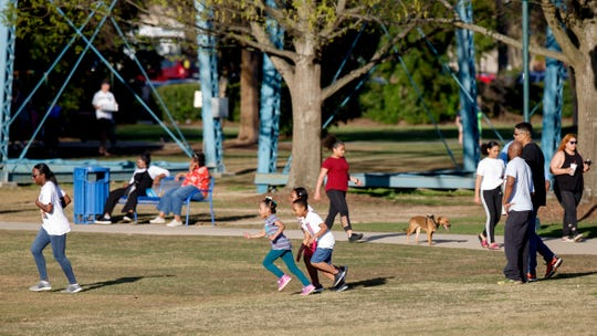 People play and enjoy the weather at Coolidge Park on Thursday, March 26, 2020, in Chattanooga, Tenn. Despite the coronavirus, people gathered at the park, albeit in smaller numbers than usual.