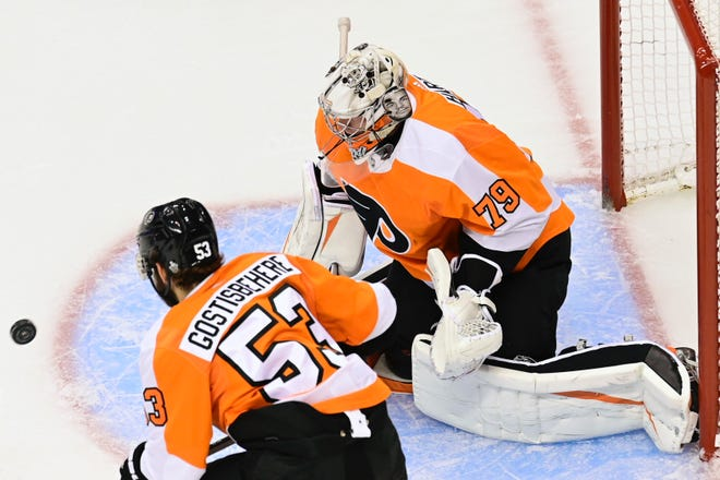 Flyers defenseman Shayne Gostisbehere and goalie Carter Hart keep a close eye on the puck during Game 2 against the Canadiens.