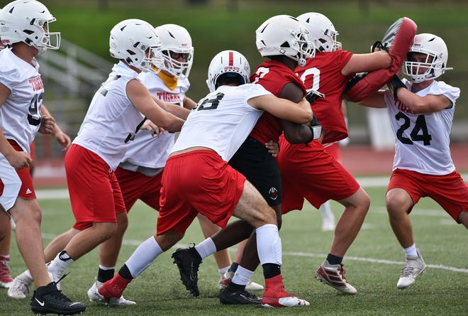 Moon Area High School's Dalton Dobyns (88), center, tackles a teammate during practice.