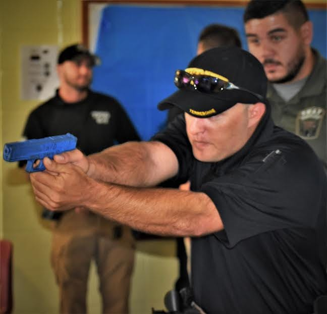 Deputy Tyler Fitch, an instructor, observes from behind as Deputy C.J. Dupre practices searching and clearing an enclosed area at a school campus. Simulated weapons are used for these training exercises to eliminate risk factors.