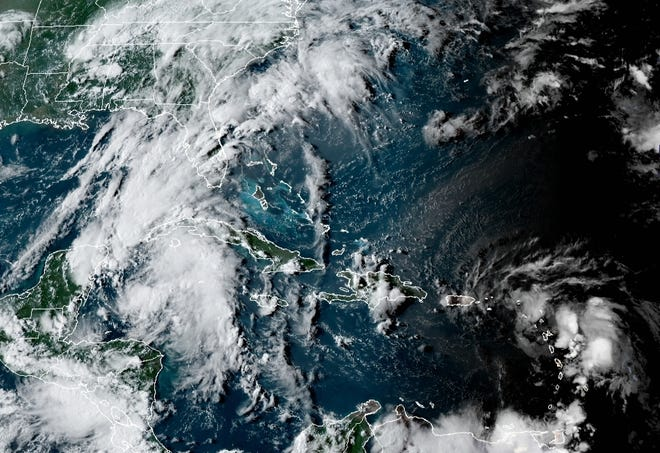 Satellite image shows Tropical Depression 14 (lower left) this afternoon in the southwest Caribbean and Tropical Storm Laura (lower right) heading west toward the sea's easternmost islands.