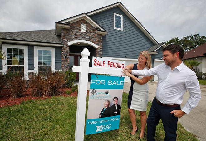 Realtors Megan Farrell-Nelson and her husband Brady Nelson of EXP Realty put a sale pending sign up in front of a house in Palm Coast on Friday, Aug. 21, 2020. The house in the Grand Landings community received multiple offers. The buyer is a woman who plans to relocate here from New York. An increase in newcomers pushed median sale prices in July to new record highs in Volusia and Flagler counties, according to area Realtor association reports.