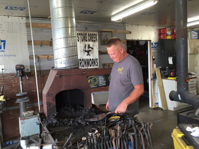 Chuck Reid works Aug. 13 inside Stone Creek Iron Works, tucked beneath a limestone cliff on County Road x99 a few miles south of his childhood home in Kingston. Although metal fabrication and welding comprise the bulk of his business, blacksmithing remains the work he enjoys most.