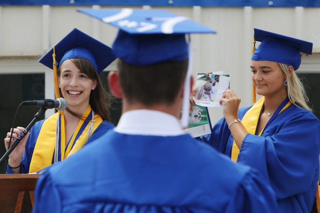 Rachel Johs, left, The Hawk Eye's Citizen Scholar of the Year, one of three class valedictorians gives her class address with the help of fellow valedictorian Taylor Ackerman, holding a daily calendar, during the 2020 Notre Dame High School graduation ceremony June 28 held on the school's track.