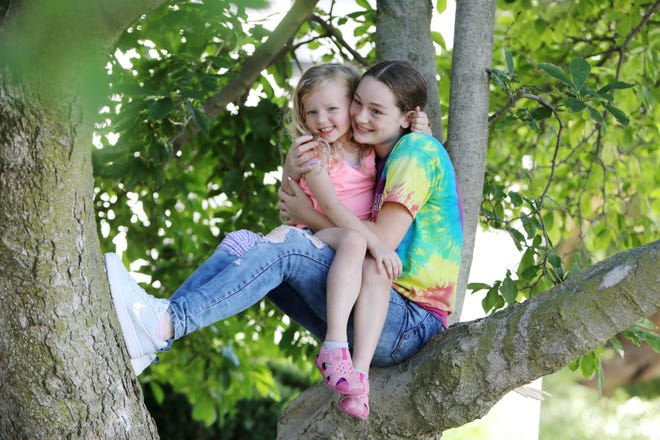 Sisters Krysstina Cassidy, 13, and Kaidance Wixom, 4, find a shady spot in a tree to keep cool Thursday in Burlington. The weekend forecast calls for temperatures approaching 90 degrees.