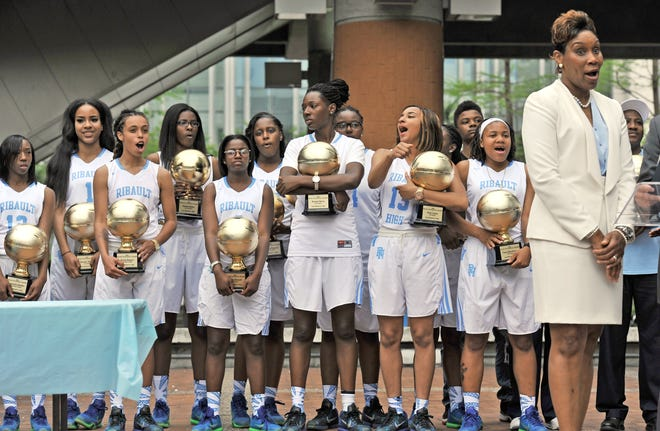 Backed by her players, Ribault head basketball coach Shelia Seymore-Pennick addresses the audience during a victory celebration and parade in Hemming Park on April 12, 2016, in recognition of their national championship.