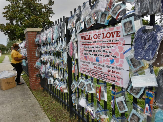 Volunteers with Wall of Love and Blessing Others All the Time erect their wall of supplies to provide necessities for people in need Friday outside the Clara White Mission in Jacksonville.