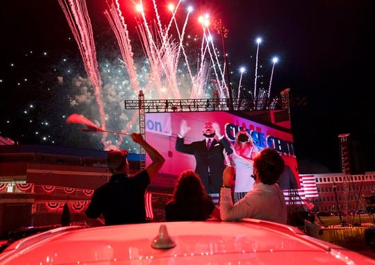 Supporters cheer from their cars as Democratic presidential candidate former Vice President Joe Biden and his wife Jill Biden are seen on a huge monitor as fireworks light up the nigh sky on the fourth day of the Democratic National Convention, Thursday, Aug. 20, 2020, outside of the Chase Center in Wilmington, Del. (AP Photo/Carolyn Kaster)