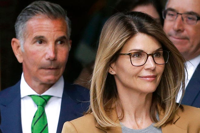 FILE - In this April 3, 2019 file photo, actress Lori Loughlin, front, and husband, clothing designer Mossimo Giannulli, left, depart federal court in Boston after facing charges in a nationwide college admissions bribery scandal. The famous couple pleaded guilty to charges in May 2020, and both were sentenced to prison time on Friday, Aug. 21, 2020.