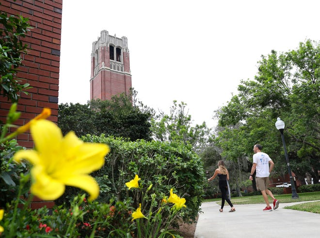 People walk past a stand of lilies near Century Tower and the University Auditorium at the University of Florida campus on April 8 while the campus was for the most part empty due to the coronavirus pandemic. While some public universities are set to open on Monday, UF begins its fall semester on Aug. 31.