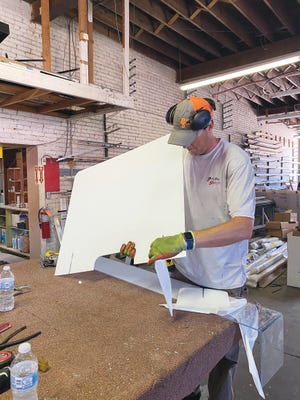 Pratt Glass Enterprises lead glazier Patrick Peterson is at work creating a personal protection plexi-glass shield, many of which are now in use by area schools and businesses as a COVID-19 protection measure.