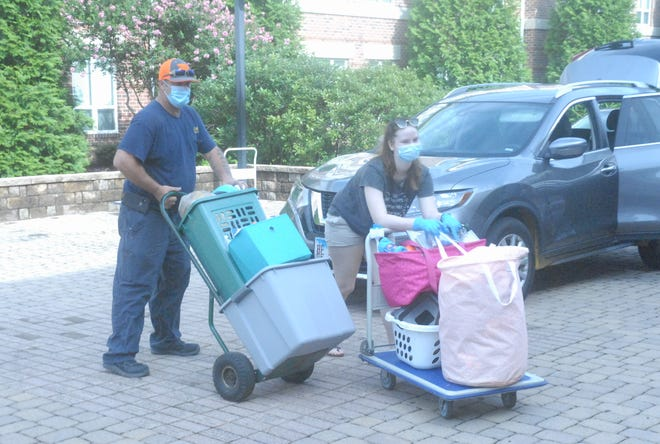 Students and parents push carts with personal items into the dormitories at Richard Bland College on Thursday.