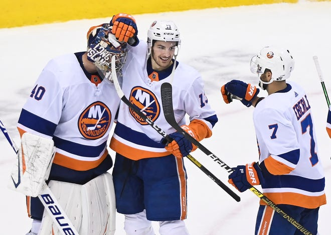 New York Islanders goaltender Semyon Varlamov, left, celebrates his shutout win and series victory with teammates Mathew Barzal and Jordan Eberle (7) after Thursday's 4-0 win against the Washington Capitals. [Nathan Denette/The Canadian Press via AP]