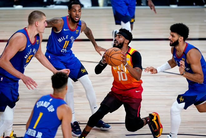 Utah Jazz's Mike Conley looks for an opening against Denver's Michael Porter Jr. (1), Nikola Jokic (15), Monte Morris (11) and Jamal Murray during the first half of Friday's playoff game in Lake Buena Vista, Fla. [AP Photo/Ashley Landis, Pool]