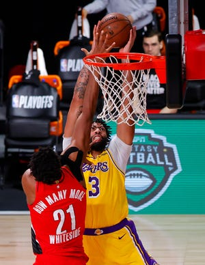 Portland's Hassan Whiteside (21) blocks a dunk attempt by Los Angeles' Anthony Davis during the third quarter of Thursday's game in Lake Buena Vista, Fla., but Davis scored 31 points in the Lakers' 111-88 win. [Kevin C. Cox/Pool Photo via AP]