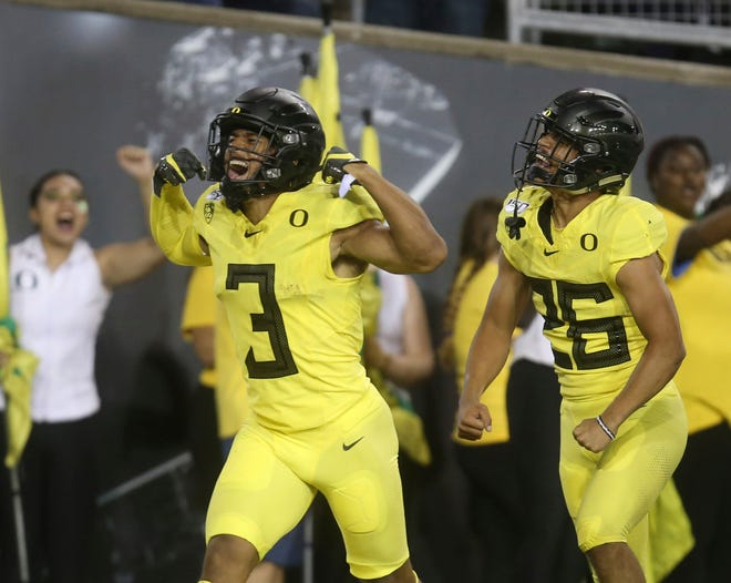 Oregon's Johnny Johnson (3) celebrates a touchdown against Montana with teammate Travis Dye during the first half of a Sept. 14 game at Autzen Stadium. Johnson, a senior, could return to the Ducks for the 2021 fall season even if he plays in the spring. [Chris Pietsch/The Register-Guard]