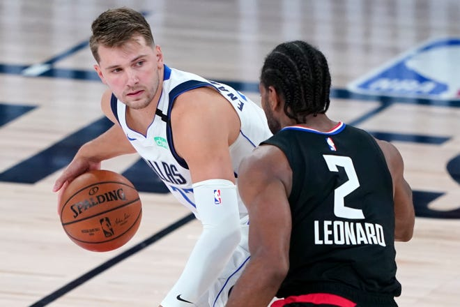 Dallas' Luka Doncic is defended by the Los Angeles Clippers' Kawhi Leonard (2) during the second half of Wednesday's playoff game in Lake Buena Vista, Fla. The two teams play again Friday night with the series tied 1-1. (AP Photo/Ashley Landis, Pool)