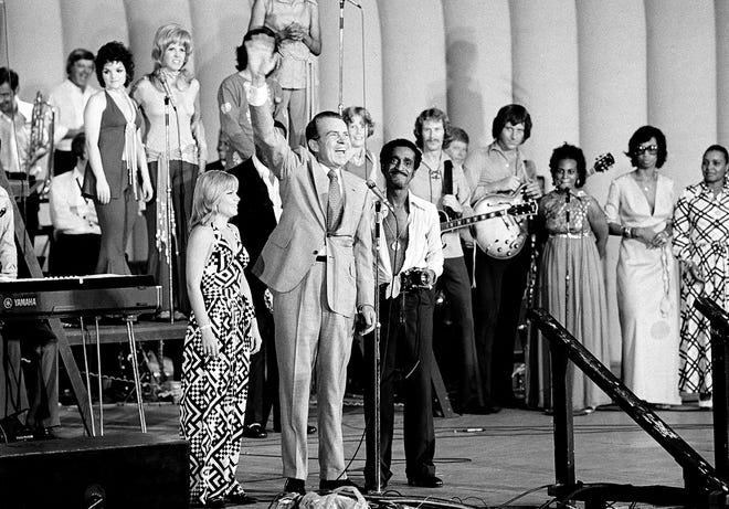 President Richard M. Nixon waves to an estimated 8,000 of his youthful supporters at a youth rally in Marine Stadium on Aug. 22, 1972, in Miami Beach after the Republican National Convention nominated him for re-election. With him are Pam Powell, head of Young Voters for the President, and Sammy Davis Jr., the rally master of ceremonies.