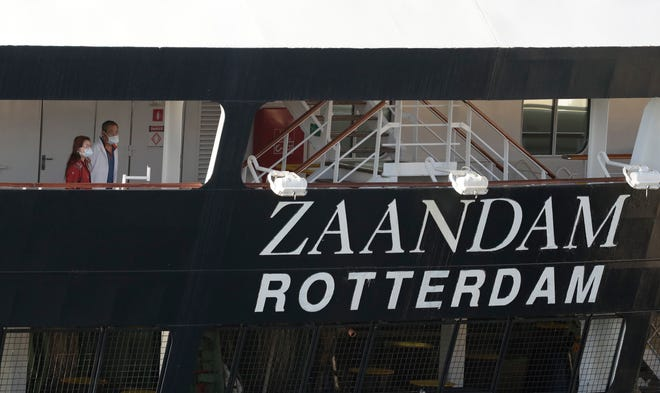 Two people look off the stern of the Holland America cruise ship Zaandam after it docked at Port Everglades, in Fort Lauderdale, April 2, 2020. The ship, carrying hundreds of passengers, was trapped at sea when the coronavirus pandemic was declared in March.
