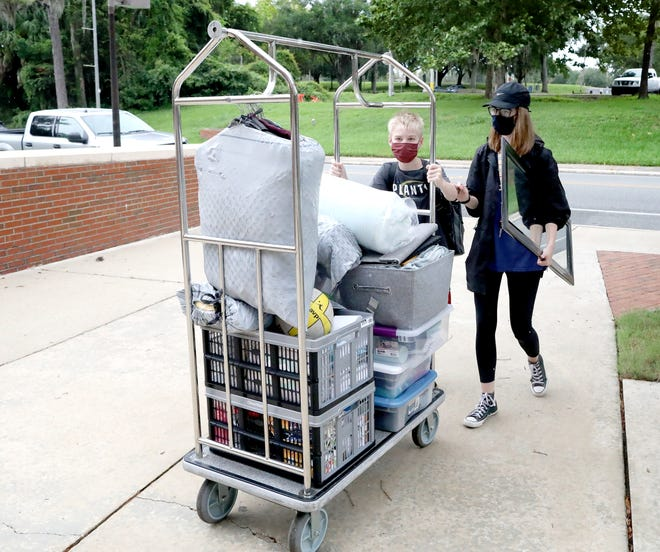 Greta Schmitzer, 18, an incoming freshman majoring in journalism, walks with her brother Owen as he pushes a luggage cart with Greta's belongings to her dorm in Hume Hall on the first day of move-in for University of Florida students on Friday.