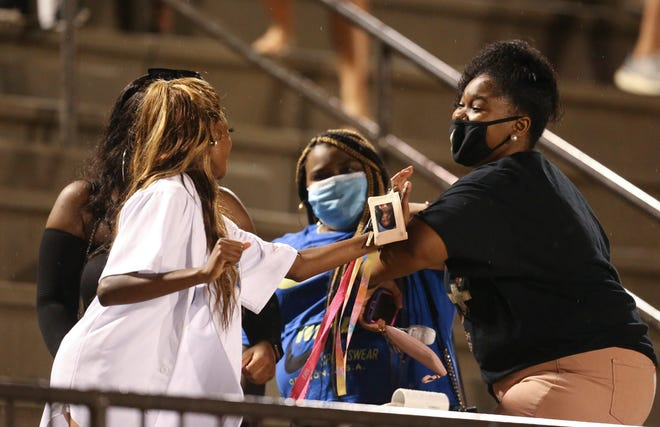 Fans, coaches, players and cheerleaders took a mixed approach to social distancing and mask wearing requirements Friday night as Tuscaloosa County High played Paul Bryant High Thursday, August 20, 2020, at Tuscaloosa County. Fans wearing masks give each other an elbow bump greeting.  [Staff Photo/Gary Cosby Jr.]