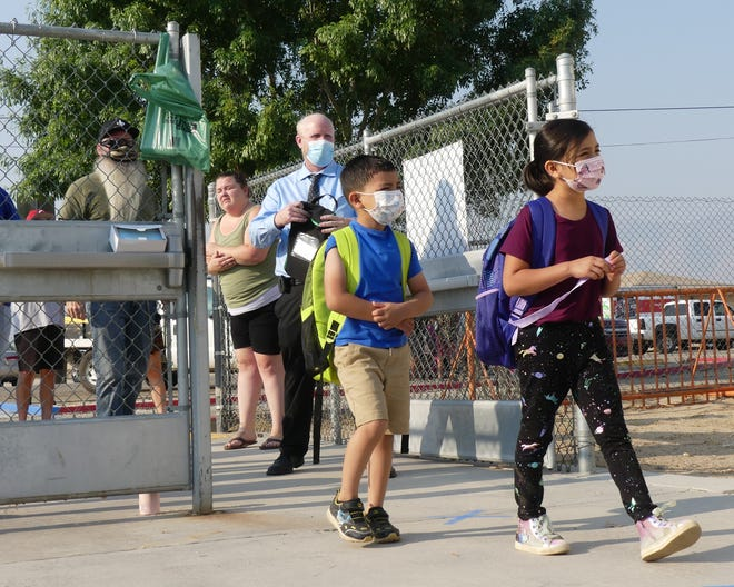 Students walk onto the Lucerne Valley Elementary School campus on Thursday, Aug. 20, 2020. The school was allowed to reopen amid the COVID-19 pandemic after receiving an approved waiver from the state of California.