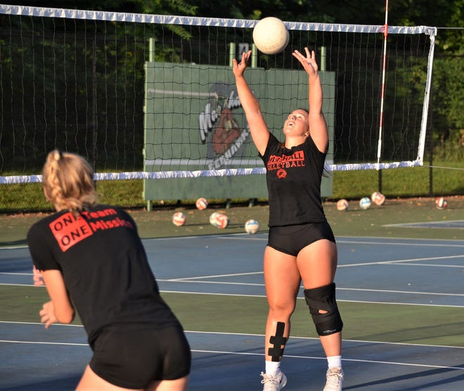 Marshall setter Teagan Giannunzio works through a drill during volleyball practice on the tennis courts Friday at Marshall High School
